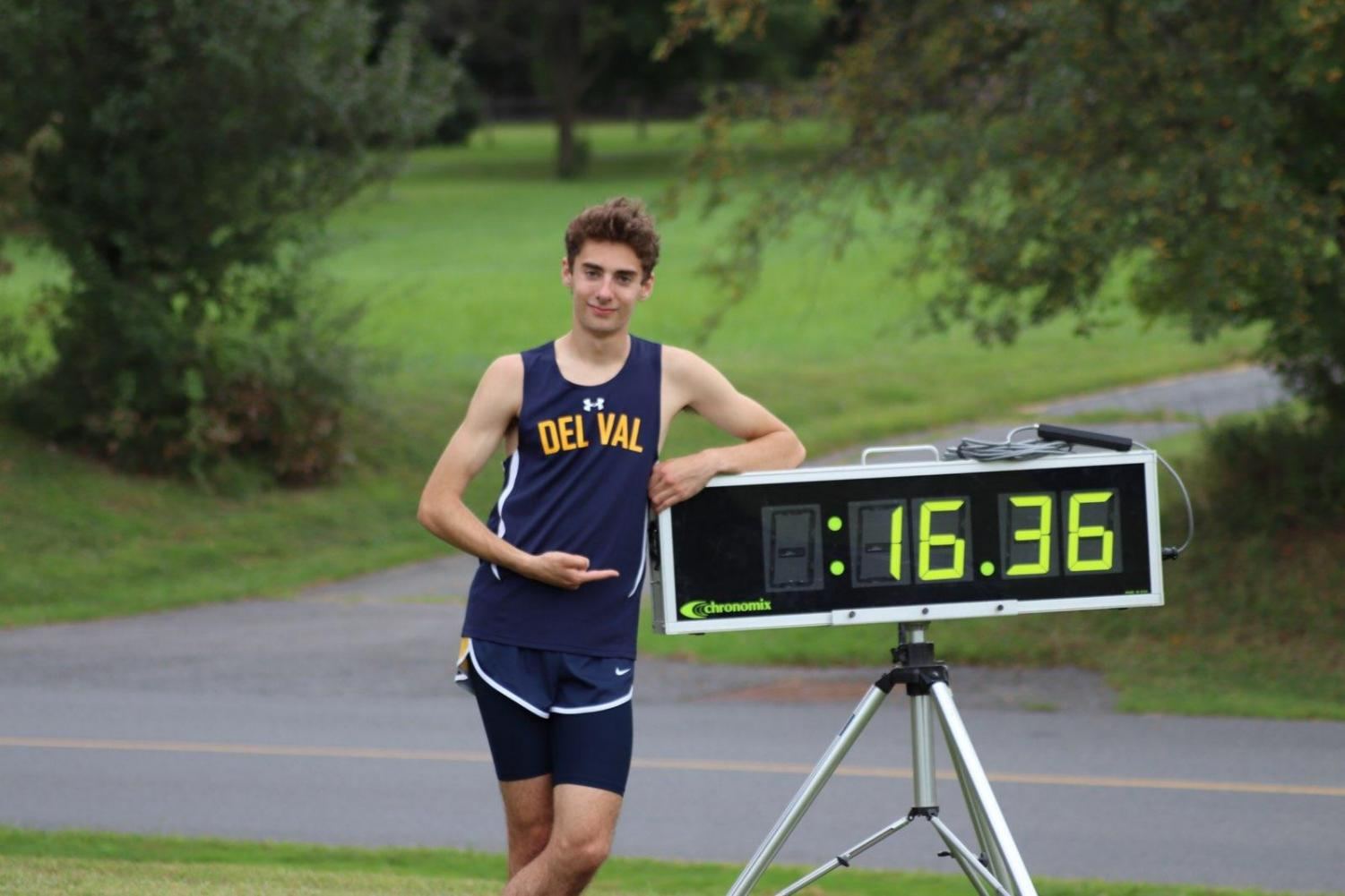 Boys Cross Country runner, Kyle Reers, stands proud next to his record breaking time.