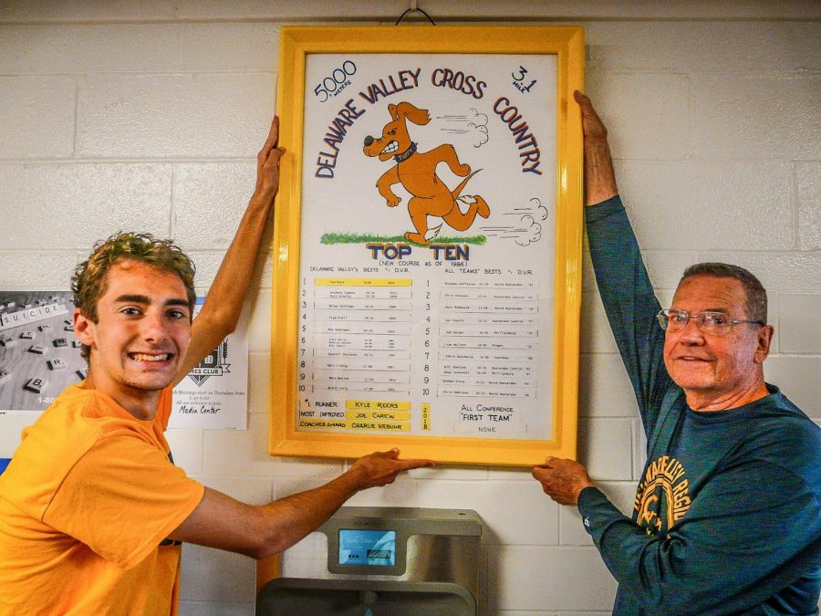 Senior Kyle Reers (left) and Coach Petty (right) hanging cross country plaque with Kyle's new record.