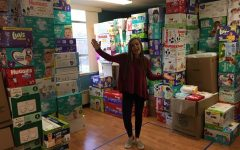 Lucy Nugent next to the many diapers donated to her Diaper Drive.