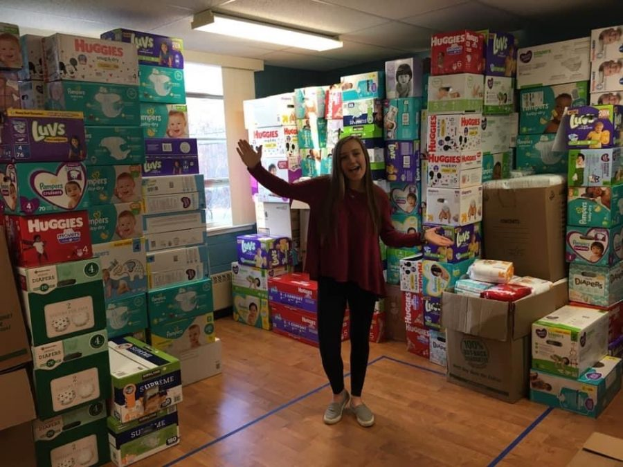 Lucy+Nugent+next+to+the+many+diapers+donated+to+her+Diaper+Drive.+